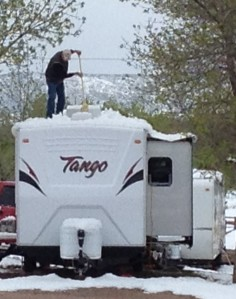 Our campground neighbor clearing snow from the top of his RV.